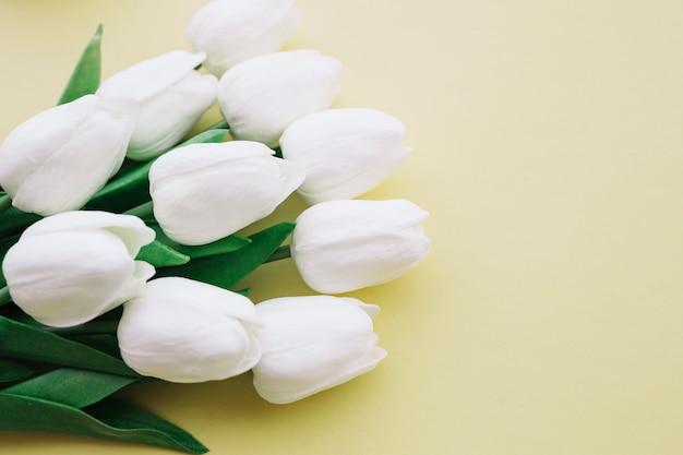 Bouquet de tulipes blanches sur fond jaune