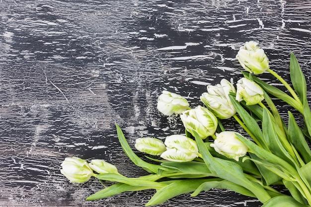 Bouquet de tulipes blanches sur fond noir. espace de copie, vue de dessus