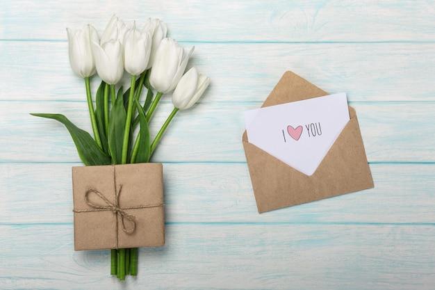 Un bouquet de tulipes blanches avec une note d'amour et enveloppe sur des planches en bois bleues