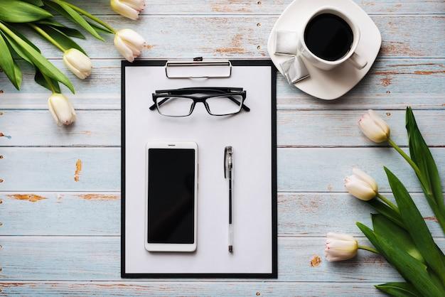 Bouquet de tulipes blanches avec un smartphone, une tasse de café et une tablette en papier sur une table en bois