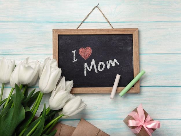 Un bouquet de tulipes blanches avec un tableau noir, enveloppes de boîte cadeau sur des planches en bois bleus. fête des mères