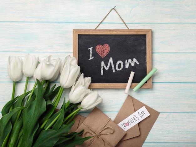 Un bouquet de tulipes blanches avec un tableau noir, une note d'amour et des enveloppes sur des planches en bois bleues. fête des mères