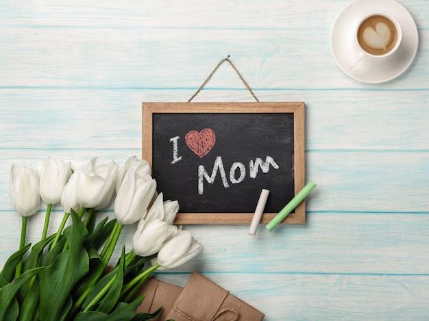 Un bouquet de tulipes blanches avec un tableau noir, une tasse de café, une note d'amour et des enveloppes sur des planches en bois bleues. fête des mères