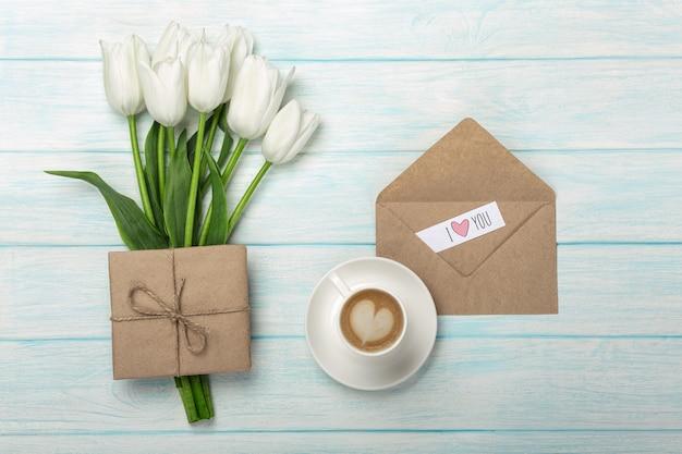 Un bouquet de tulipes blanches, une tasse de café avec une note d'amour et une enveloppe sur des planches en bois bleu