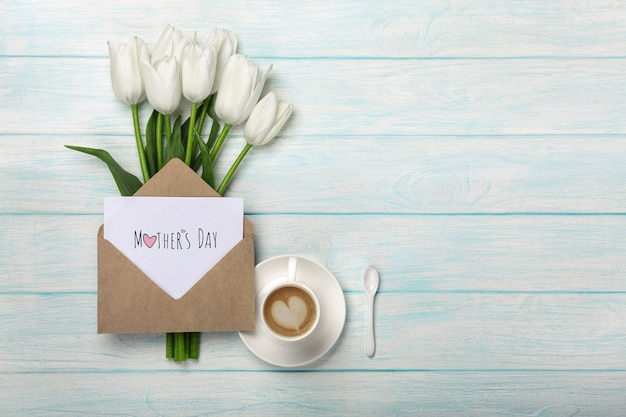 Un bouquet de tulipes blanches, une tasse de café avec une note d'amour et une enveloppe sur des planches en bois bleues. fête des mères