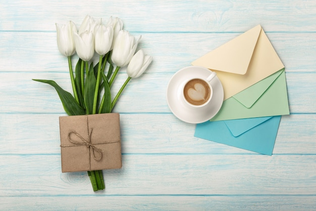 Un bouquet de tulipes blanches, une tasse de café avec une note d'amour et des enveloppes de couleurs sur des planches en bois bleues. fête des mères