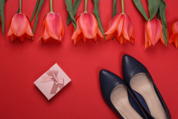 Bouquet de tulipes et chaussures à talons hauts, coffret cadeau sur fond rouge. fête des mères ou 8 mars, anniversaire. vue de dessus