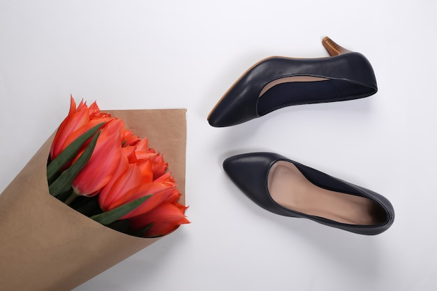Bouquet de tulipes et chaussures à talons hauts sur fond blanc. fête des mères ou 8 mars, anniversaire. vue de dessus