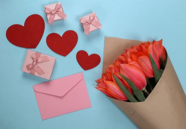 Bouquet de tulipes et coeurs, coffrets cadeaux, enveloppes sur fond bleu. fête des mères, 8 mars, anniversaire ou saint valentin, demande en mariage. vue de dessus