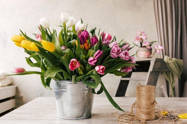 Bouquet de tulipes. contexte en milieu de travail de fleuriste. fleurs colorées, outils dans un intérieur blanc. préparation à la création du bouquet. fleuriste, décorateur, bricolage, artisanat, concept de cadeau de printemps