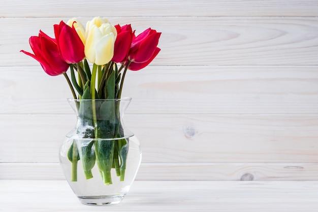 Bouquet de tulipes dans un vase sur fond en bois. lieu vide pour le texte.
