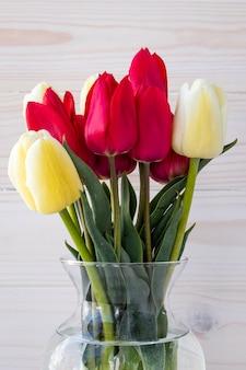 Bouquet de tulipes dans un vase en verre sur une table en bois blanc. bouquet de fleurs colorées.