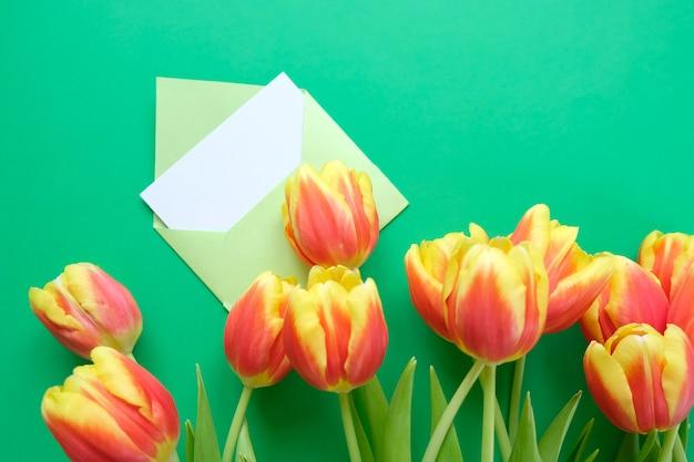 Un bouquet de tulipes et une enveloppe avec une note sur fond vert. concept de la journée internationale de la femme, fête des mères, pâques