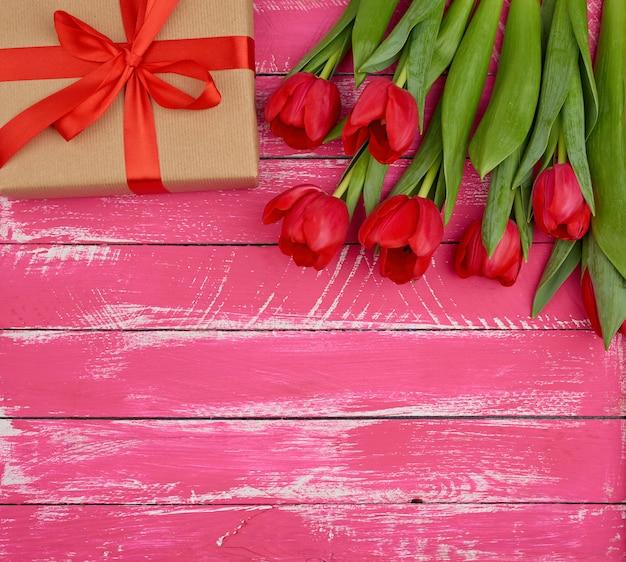 Bouquet de tulipes en fleurs rouges avec des feuilles vertes, cadeau emballé dans du papier kraft brun