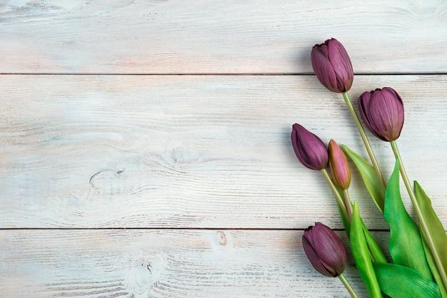 Bouquet de tulipes sur fond de bois clair.