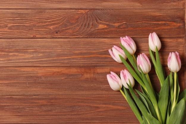 Un bouquet de tulipes sur fond de bois vue de dessus fond de printemps