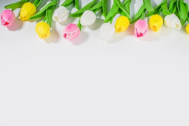 Bouquet de tulipes de fond de pâques, grand bouquet de fleurs de tulipes colorées sur fond de table blanche vue de dessus de l'espace de copie pour le texte. motif de fleurs de vacances de printemps