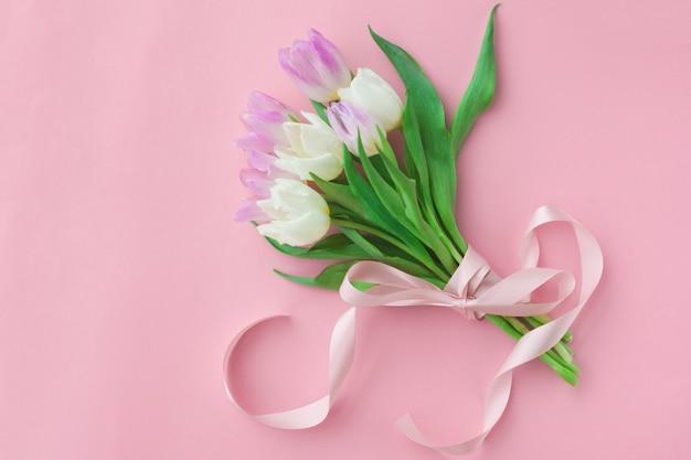 Bouquet de tulipes sur fond rose pastel.