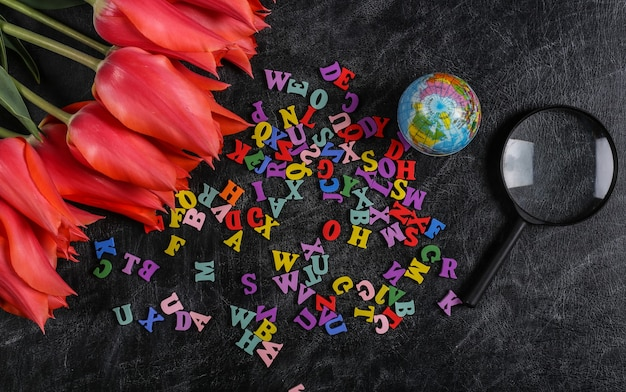 Bouquet de tulipes et fournitures scolaires, lettres sur tableau noir. journée du savoir, retour à l'école. vue de dessus