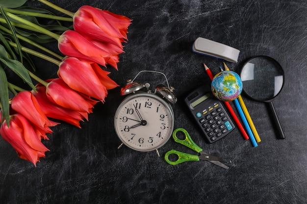 Bouquet de tulipes et fournitures scolaires sur tableau noir. connaissances, journée des enseignants, retour à l'école. vue de dessus