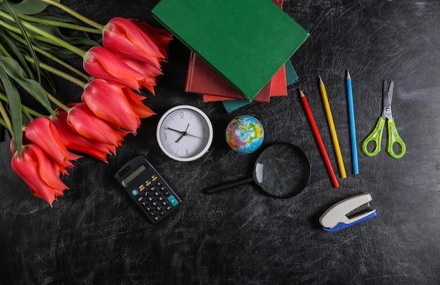 Bouquet de tulipes et fournitures scolaires sur tableau noir. connaissances, journée des enseignants, retour à l'école