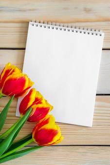 Bouquet de tulipes fraîches et carte vierge vide pour l'espace de copie sur fond de table en bois.