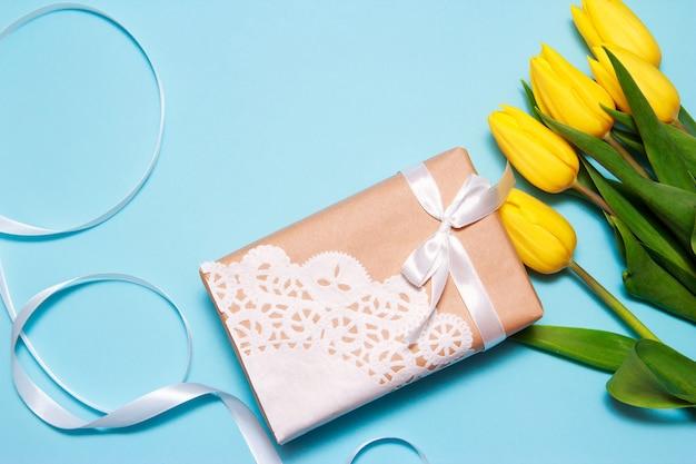 Un bouquet de tulipes jaunes et un cadeau de papier kraft décoré avec une serviette en dentelle sur un fond de papier bleu.