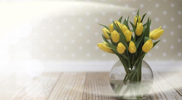 Bouquet de tulipes jaunes dans un vase au sol