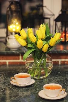 Un bouquet de tulipes jaunes dans un vase à l'intérieur d'une pièce rétro. intérieur rétro avec bouquet de tulipes.