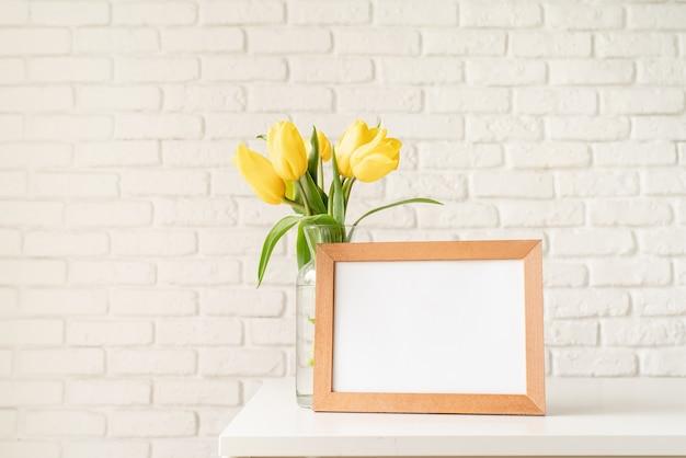 Bouquet de tulipes jaunes dans un vase en verre et cadre photo vierge sur fond de mur de briques blanches. conception de maquette