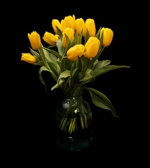 Bouquet de tulipes jaunes dans un vase en verre sur fond noir. belles fleurs. . cadeau féminin. la saint valentin. 8 mars. photo de haute qualité