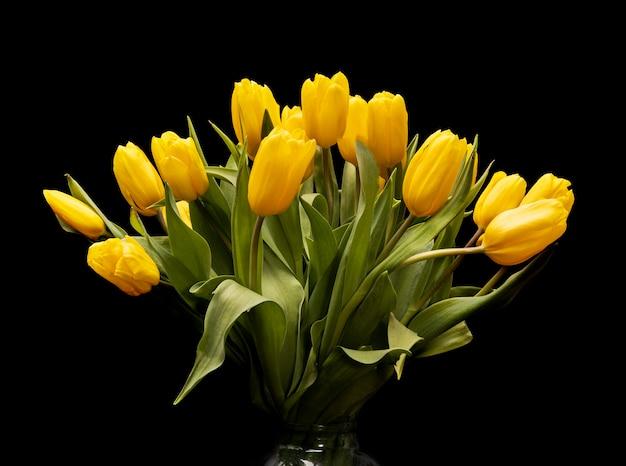 Bouquet de tulipes jaunes dans un vase en verre sur fond noir. belles fleurs. plante de jardin. cadeau féminin. la saint valentin. photo de haute qualité