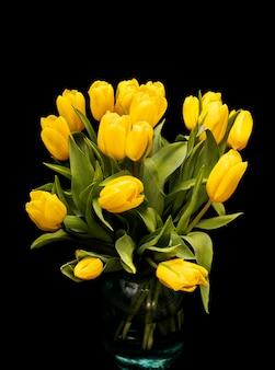 Bouquet de tulipes jaunes dans un vase en verre sur fond noir. belles fleurs. plante de jardin. la saint-valentin. photo de haute qualité