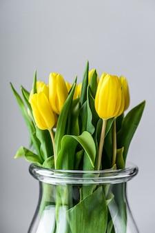 Un bouquet de tulipes jaunes dans un vase en verre