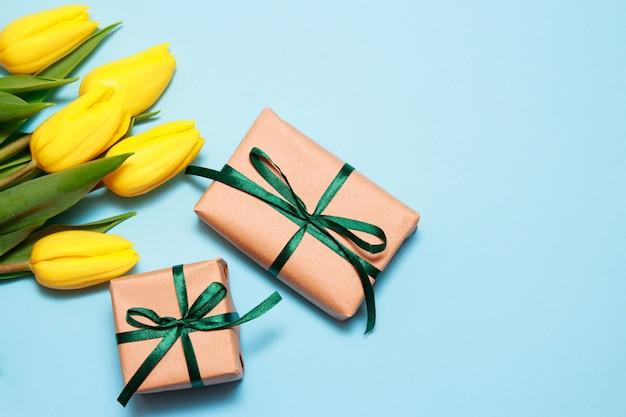 Un bouquet de tulipes jaunes et deux cadeaux d'artisanat sur un fond de papier bleu.
