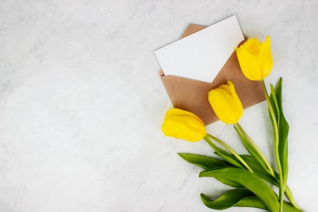 Bouquet de tulipes jaunes, enveloppe et lettre à plat sur fond de marbre