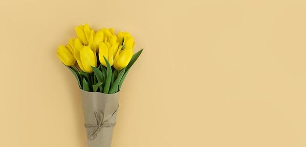 Bouquet de tulipes jaunes enveloppées dans du papier kraft sur fond beige avec copyspace.