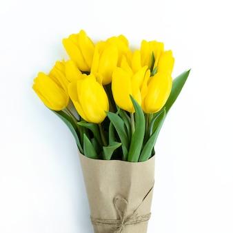 Bouquet de tulipes jaunes enveloppées de papier kraft sur fond blanc.