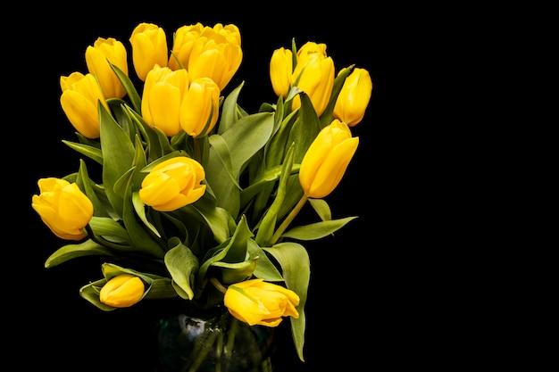 Bouquet de tulipes jaunes sur fond noir. photo de haute qualité