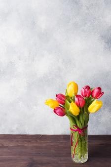 Bouquet de tulipes jaunes et roses dans un vase sur fond gris. fond pour produit et texte.