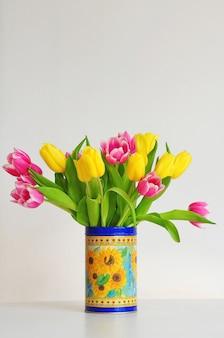 Bouquet de tulipes jaunes et roses dans un vase.