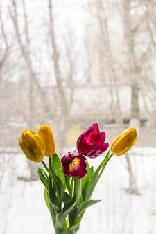 Un bouquet de tulipes jaunes et roses envahit le rebord de la fenêtre. un cadeau de fleurs par la fenêtre.