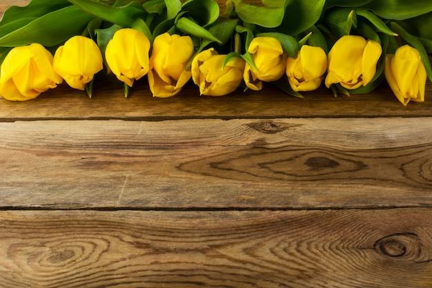 Bouquet de tulipes jaunes sur une surface en bois, espace de copie