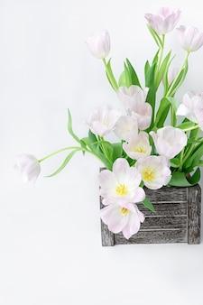 Un bouquet de tulipes légèrement roses dans une boîte en bois sur un fond blanc.