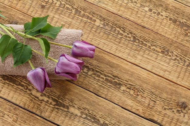 Bouquet de tulipes lilas sur un sac et des planches de bois. vue de dessus. concept de donner un cadeau en vacances.