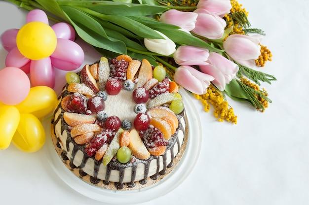 Bouquet de tulipes et mimosa, ballons comme fleurs et grand gâteau à la crème aux fruits