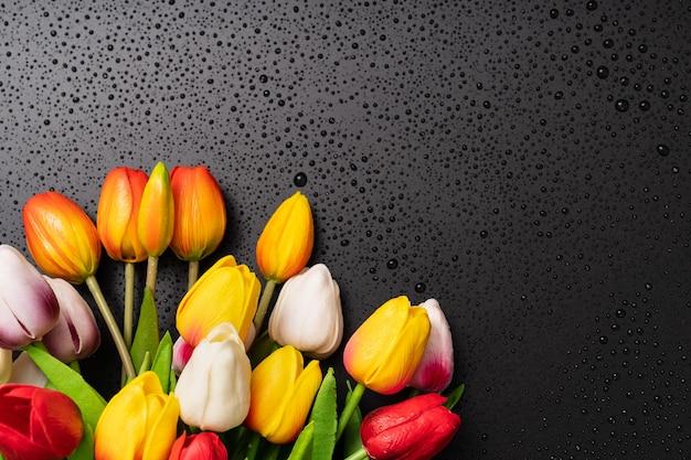 Bouquet de tulipes multicolores et gouttes d'eau sur fond noir. texture. rosée à la surface. mouillage. gouttes après la pluie ou le brouillard.