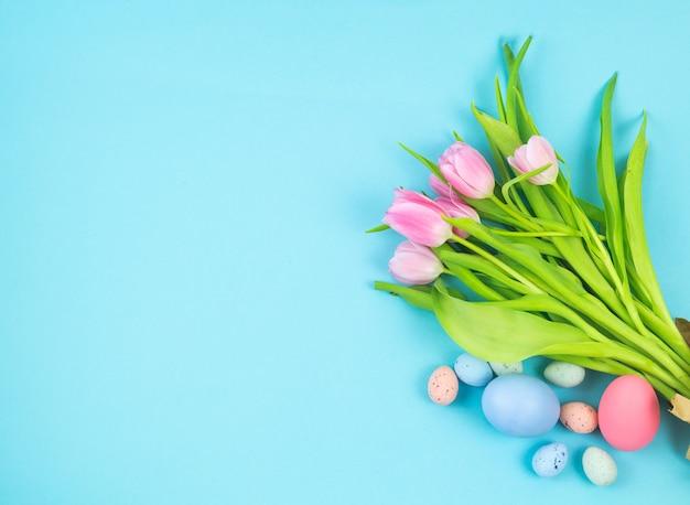 Bouquet de tulipes et oeufs de pâques sur fond bleu copiez l'espace.