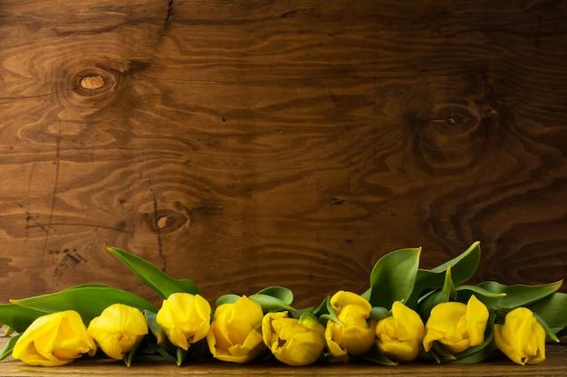 Bouquet de tulipes printanières sur une surface en bois, espace copie