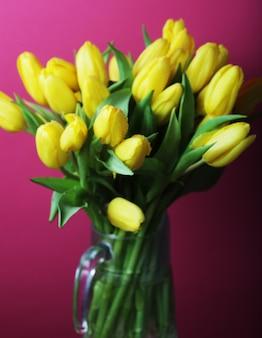 Bouquet de tulipes de printemps dans un vase en verre avec de l'eau
